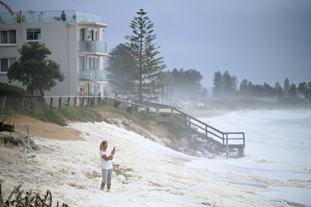 A resident inspects sea foam brought by waves approaching on beach front houses after heavy rain and storms at Collaroy in Sydney's Northern Beaches, Monday, February 10, 2020. Drought, wildfires and now flooding have given Australia's weather an almost Biblical feel this year. The good news is that a deluge in eastern parts of the country over recent days has helped dampen deadly fires and ease a crippling drought. (Joel Carrett, AAP Image via AP)