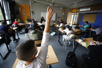 A masked schoolchild raises his arm to answer his teacher during a class in Bischheim, outside Strasbourg, eastern France, Tuesday, Sept.1, 2020. Millions of French children starting going back to class Tuesday despite a recent rise in virus infections, in a nationwide experiment aimed at bridging inequalities and reviving the economy. (AP Photo/Jean-Francois Badias)