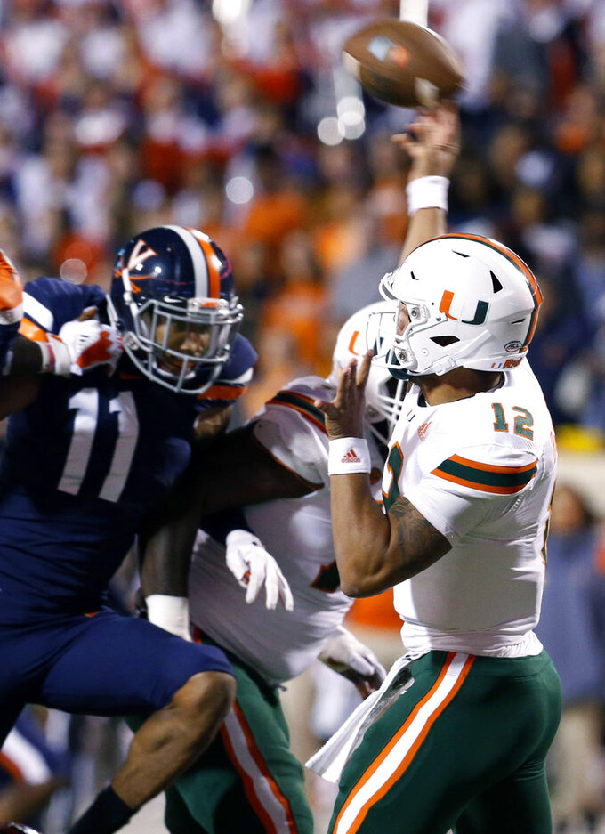 Miami quarterback Malik Rosier (12) passes as Virginia linebacker Charles Snowden (11) closes in during the first half of an NCAA college football game in Charlottesville, Va., Saturday, Oct. 13, 2018. (AP Photo/Steve Helber)