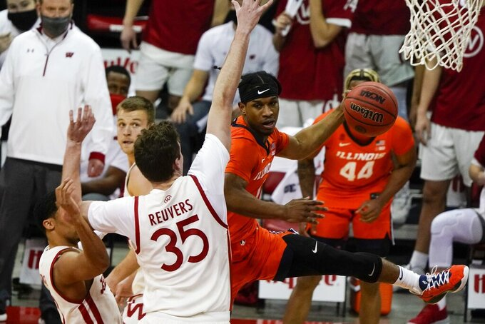 Illinois's Trent Frazier tries to pass around Wisconsin's Nate Reuvers during the first half of an NCAA college basketball game Saturday, Feb. 27, 2021, in Madison, Wis. (AP Photo/Morry Gash)
