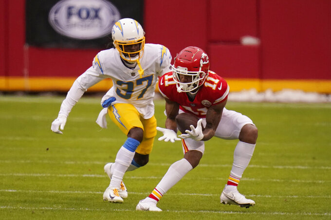 Kansas City Chiefs wide receiver Demarcus Robinson (11) catches a pass ahead of Los Angeles Chargers cornerback Tevaughn Campbell (37) during the first half of an NFL football game, Sunday, Jan. 3, 2021, in Kansas City. (AP Photo/Jeff Roberson)