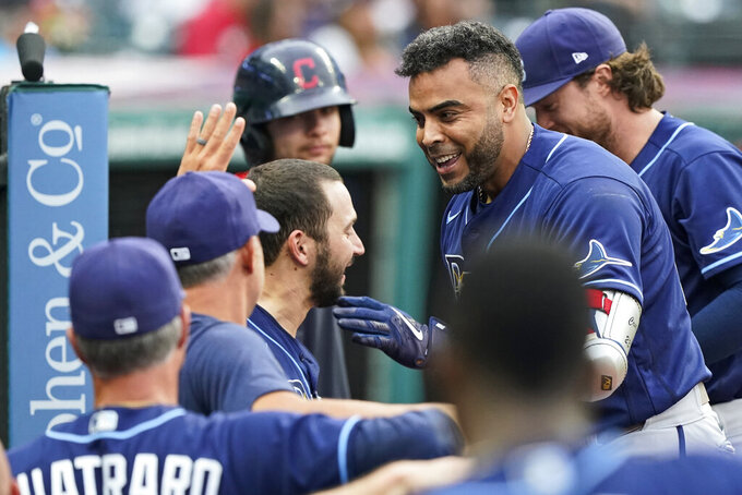 Tampa Bay Rays' Nelson Cruz is congratulated by teammates after hitting a solo home run during the third inning of the teams' baseball game against the Cleveland Indians, Friday, July 23, 2021, in Cleveland. (AP Photo/Tony Dejak)