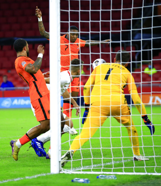 Netherlands' Steven Bergwijn, top, scores his team's first goal during the UEFA Nations League soccer match between the Netherlands and Poland in the Johan Cruyff ArenA in Amsterdam, Netherlands, Friday, Sept. 4, 2020. (AP Photo/Peter Dejong)