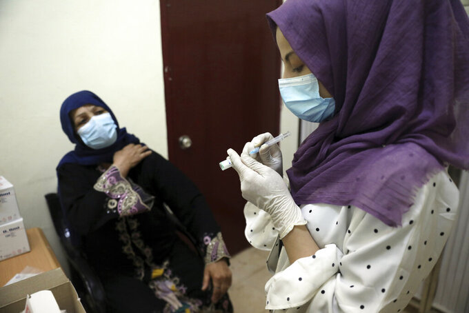 A doctor fills a syringe with the Sinopharm COVID-19 vaccine at a vaccination center in Kabul, Afghanistan, Wednesday, June 16, 2021. (AP Photo/Rahmat Gul)
