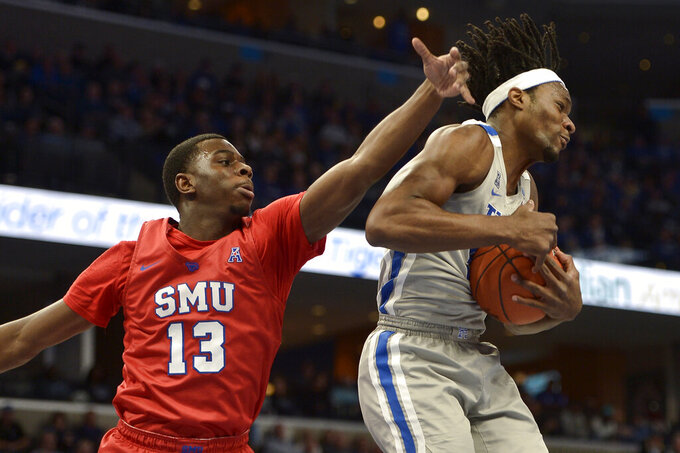 Memphis forward Precious Achiuwa, right, grabs a rebound ahead of Southern Methodist guard CJ White, left, in the first half of an NCAA basketball game Saturday, Jan. 25, 2020, in Memphis, Tenn. (AP Photo/Brandon Dill)