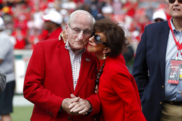 Former head Georgia football coach and athletic director Vince Dooley, left, gets a kiss from his wIfe Barbara during a ceremony to name the field at Sanford Stadium in his honor before an NCAA college football game against the Murray State, Saturday, Sept. 7, 2019, in Athens, Ga. (AP Photo/John Bazemore)