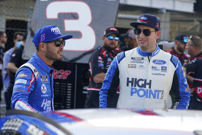 Kyle Larson, left, talks with Chase Briscoe before qualifications for the NASCAR Series auto race at Indianapolis Motor Speedway, Sunday, Aug. 15, 2021, in Indianapolis. (AP Photo/Darron Cummings)