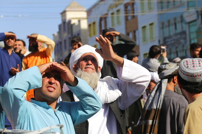 CORRECTS DAY TO SEPT 25 - People look up at a dead body hanged by the Taliban from a crane in the main square of Herat city in western Afghanistan, on Saturday Sept. 25, 2021. A witness told The Associated Press that the bodies of four men were brought to the main square and three of them were moved to other parts of the city for public display. The Taliban announced in the square that the four were caught taking part in a kidnapping and were killed by police.(AP Photo)