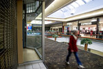 A person walks by a closed store front near an Express retail clothing store in Valley West Mall, Wednesday, Jan. 22, 2020, in West Des Moines, Iowa. Express, a staple in U.S. malls, will close about 100 stores as part of a restructuring plan as the chain grapples with drastic changes in where people spend their shopping dollars. (AP Photo/Andrew Harnik)