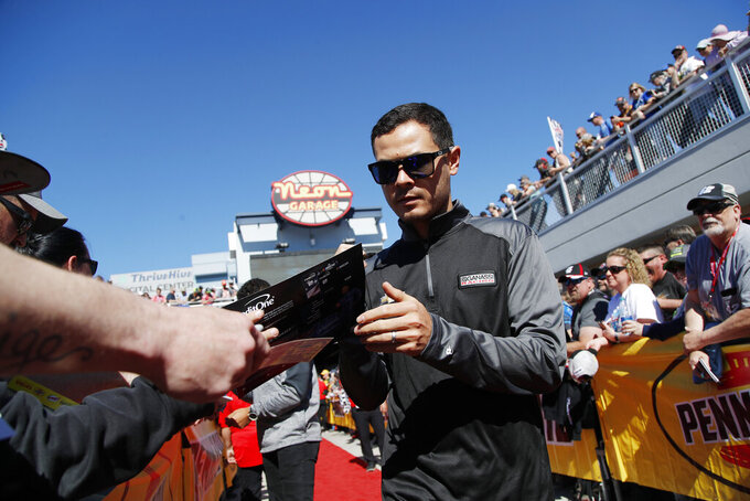 Kyle Larson gives autographs before a NASCAR Cup Series auto race at Las Vegas Motor Speedway, Sunday, March 3, 2019, in Las Vegas. (AP Photo/John Locher)