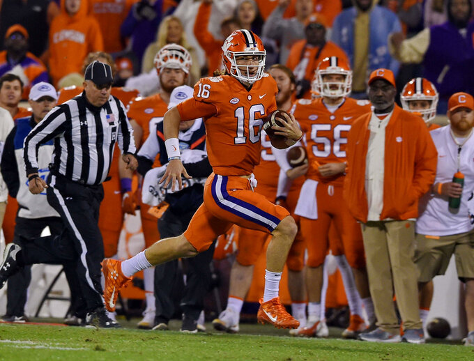 Clemson quarterback Trevor Lawrence breaks away for a long rush to gain a first down during the first half of an NCAA college football game against South Carolina Saturday, Nov. 24, 2018, in Clemson, S.C. (AP Photo/Richard Shiro)
