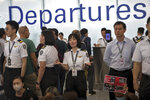 An airport security staff member gestures to travelers at the Hong Kong International Airport in Hong Kong, Tuesday, Aug. 13, 2019. Protesters clogged the departure area at Hong Kong's reopened airport Tuesday, a day after they forced one of the world's busiest transport hubs to shut down entirely amid their calls for an independent inquiry into alleged police abuse. (AP Photo/Vincent Thian)