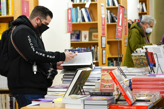 FILE- In this Saturday, Nov. 28, 2020, file photo, customers browse while shopping for books at the Strand Bookstore, an independent family owned bookstore founded in 1927 in New York. A Federal Reserve survey of business conditions around the country found that economic activity in several regions was slowing in November as coronavirus cases surged. The report, released Wednesday, Dec. 2, 2020, and known as the beige book, will be used by Fed officials when they hold their last meeting of the year on Dec. 15-16 to discuss possible changes to the central bank's interest-rate policies.. (AP Photo/Mary Altaffer)