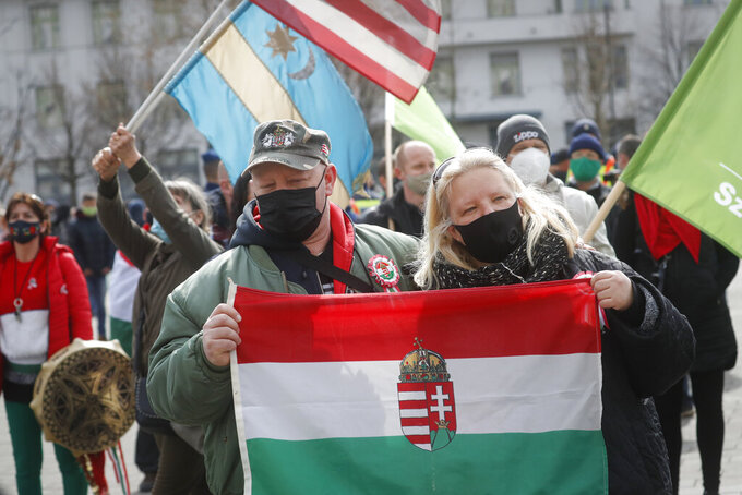 Hungarians hold flags during a protest in Budapest, Hungary, Monday, March 15, 2021. Hungarians gathered on the country's national day to protest against the current lockdown measures after new restrictive measures were introduced by the Hungarian government last week aiming to slow a record-breaking wave of COVID-19 hospitalizations and deaths. (AP Photo/Laszlo Balogh)