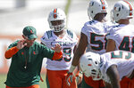 File-This Aug. 4, 2016, file photo shows Miami defensive coordinator Manny Diaz, left, giving instructions to players during drills at the NCAA college football team's practice, in Coral Gables, Fla.  Diaz will serve as Miami's defensive coordinator for one final game before he leaves for good as the new head coach at Temple. Diaz managed to show a rare loyalty to the program that few departing coaches share while also remaining fully engaged in his new job: the Owls received 17 commitments during the early signing period. (AP Photo/Alan Diaz, File)