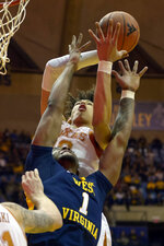 Texas forward Jaxson Hayes, top, catches a rebound as West Virginia forward Derek Culver (1) reaches during the first half of an NCAA college basketball game in Morgantown, W.Va., Saturday, Feb. 9, 2019. (AP Photo/Craig Hudson)