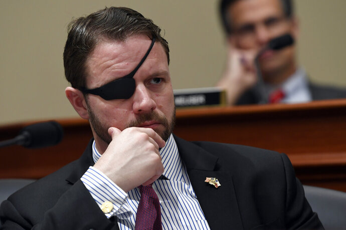 """FILE - In this Tuesday, March 12, 2019, file photo, U.S. Rep. Dan Crenshaw, R-Texas, left, listens as Office of Management and Budget Acting Director Russell Vought testifies before the House Budget Committee on Capitol Hill in Washington, during a hearing on the fiscal year 2020 budget. Crenshaw has a book out in April 2020. The former Navy SEAL's book is called """"Fortitude,"""" and will combine personal memories and """"no-nonsense"""" advice as Crenshaw addresses today's growing political and cultural divisions. (AP Photo/Susan Walsh, File)"""