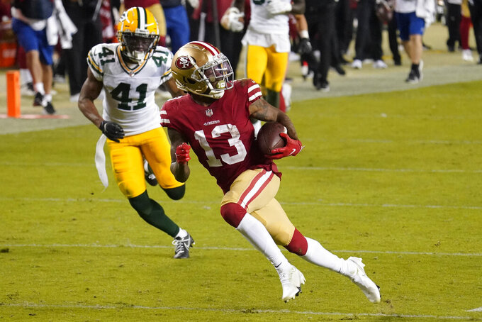 San Francisco 49ers wide receiver Richie James (13) runs in front of Green Bay Packers safety Henry Black (41) to score a touchdown during the second half of an NFL football game in Santa Clara, Calif., Thursday, Nov. 5, 2020. (AP Photo/Tony Avelar)
