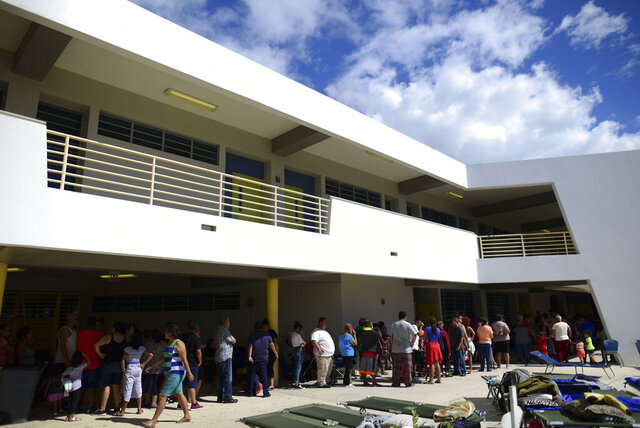 People whose homes are unsafe to enter after the previous day's magnitude 6.4 earthquake line up for lunch in an outdoor area of the Bernardino Cordero Bernard High School, which is being used as a shelter despite no electricity in Ponce, Puerto Rico, Wednesday, Jan. 8, 2020. More than 250,000 Puerto Ricans remained without water on Wednesday and another half a million without power, which also affected telecommunications. (AP Photo/Carlos Giusti)