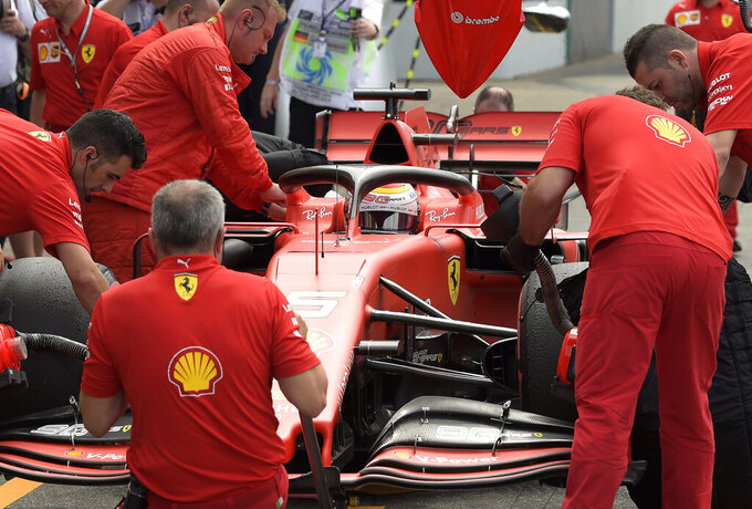 Pit crew works on the car of Ferrari driver Sebastian Vettel of Germany during the third Formula One practice session at the Hockenheimring racetrack in Hockenheim, Germany, Saturday, July 27, 2019. The German Formula One Grand Prix will be held on Sunday. (AP Photo/Jens Meyer)