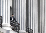 A man standing on a balcony overlooks Wall Street, Thursday, July 30, 2020, in New York. Stocks are falling on Wall Street Thursday after reports showed that layoffs are continuing at a stubborn pace and that the U.S. economy contracted at a nearly 33% annual rate in the spring. (AP Photo/Mark Lennihan)