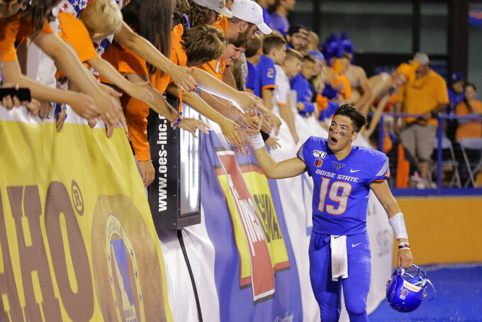 Boise State quarterback Hank Bachmeier high-fives fans after the team's NCAA college football game against Marshall in Boise, Idaho, Friday, Sept. 6, 2019. Boise State won 14-7. (AP Photo/Otto Kitsinger)