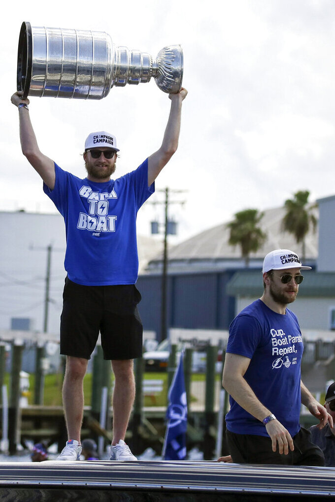 Tampa Bay Lightning center Steven Stamkos holds up the Stanley Cup as teammate defenseman Victor Hedman, right, looks on as they celebrate the teams Stanley Cup victory with a boat parade Monday, July 12, 2021 in Tampa, Fla. (Dirk Shadd/Tampa Bay Times via AP)