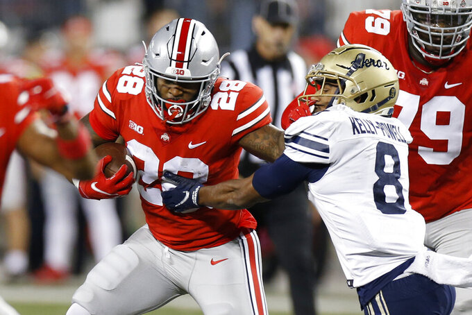 Ohio State running back Miyan Williams, left, fights his ways across the line of scrimmage against Akron defensive back Jaylen Kelly-Powell during the first half of an NCAA college football game Saturday, Sept. 25, 2021, in Columbus, Ohio. (AP Photo/Jay LaPrete)
