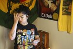 Seanna Leilani Chavez, the sister of Aaron Francisco Chavez, pauses as she looks at family photos as she stands next to a shrine for Aaron, including images of Aaron on the wall, at the family home Wednesday, Feb. 6, 2019, in Tucson, Ariz. Aaron Chavez died of a fentanyl overdose at the age of 19. (AP Photo/Ross D. Franklin)