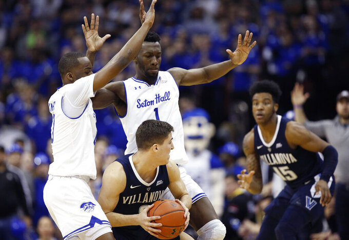 Seton Hall guard Quincy McKnight (0) and Seton Hall forward Mihael Nzei (1) double team Villanova guard Collin Gillespie (2) who looks to pass to Villanova forward Saddiq Bey (15) during the second half of an NCAA college basketball game, Saturday, March 9, 2019, in Newark, N.J. Seton Hall defeated Villanova 79-75. (AP Photo/Kathy Willens)