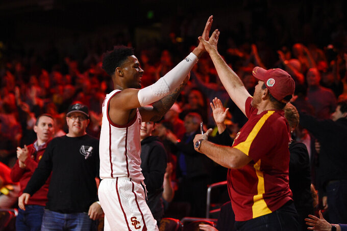 Southern California guard Elijah Weaver celebrates with a fan after USC defeated Stanford 82-78 in overtime in an NCAA college basketball game in Los Angeles, Saturday, Jan. 18, 2020. (AP Photo/Kelvin Kuo)