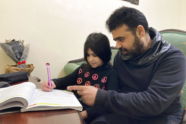 Syrian refugee Mahmoud Mansour, 47, helps his youngest daughter Sahar, 8, with her homework at his rented apartment in Amman, Jordan, Wednesday, Jan. 20, 2021. President Joe Biden has vowed to restore America's place as a world leader in offering sanctuary to the oppressed by raising the cap on the number of refugees allowed in each year. Mansour's family had completed the work to go to the United States when the Trump administration issued its travel ban barring people from Syria indefinitely and suspending the refugee program for 120 days. (AP Photo/Omar Akour)