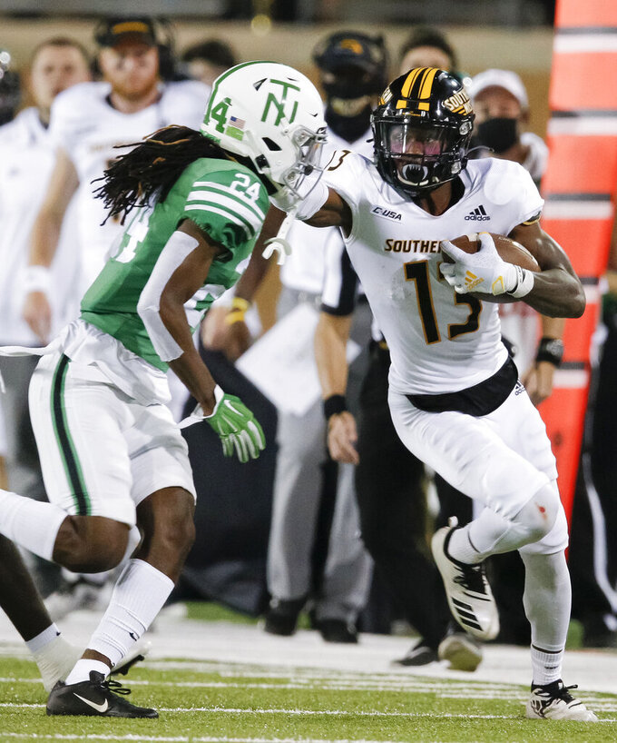 Southern Mississippi wide receiver Antoine Robinson (13) looks for room against North Texas defensive back Quinn Whitlock (24) during the second half of an NCAA college football game on Saturday, Oct. 3, 2020 in Denton, Texas. (AP Photo/Brandon Wade)
