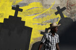 A man walks past a mural being painted by students from the National School of the Arts to express solidarity with those killed during a month of protests demanding the president's resignation in Port-au-Prince, Haiti, Tuesday, Oct. 15, 2019. President Jovenel Moïse broke his silence Tuesday and said it would be irresponsible for him to resign amid Haiti's unrest, which has entered a fifth week of deadly protests that have paralyzed the economy and shuttered schools. (AP Photo/Rebecca Blackwell)