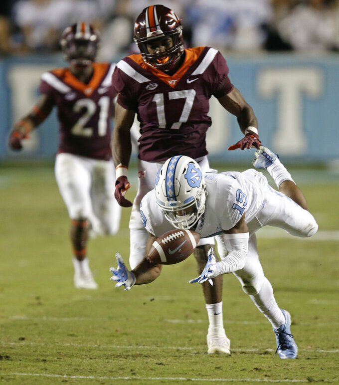 North Carolina's Dazz Newsome (19) reaches for a pass while Virginia Tech's Josh Jackson (17) defends during the first half of an NCAA college football game in Chapel Hill, N.C., Saturday, Oct. 13, 2018. (AP Photo/Gerry Broome)