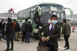In this Thursday, April 2, 2020, photo, a man disembarks from a bus at an expressway gate at the border of Wuhan city in central China's Hubei province. Millions of Chinese workers are streaming back to factories, shops and offices but many still face anti-coronavirus controls that add to their financial losses and aggravation. In Wuhan police require a health check and documents from employers for returning workers. (AP Photo/Ng Han Guan)