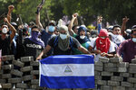Masked protesters, one with a Nicaraguan flag, yell from the road block they erected as they face off with security forces near the University Politecnica de Nicaragua (UPOLI) in Managua, Nicaragua, Saturday, April 21, 2018. Nicaraguan President Daniel Ortega said Saturday that his government is willing to enter into talks over social security reforms that have sparked four days of protests and clashes in which, rights monitors say, at least 25 people have died. A journalist covering the unrest was also killed. (AP Photo/Alfredo Zuniga)