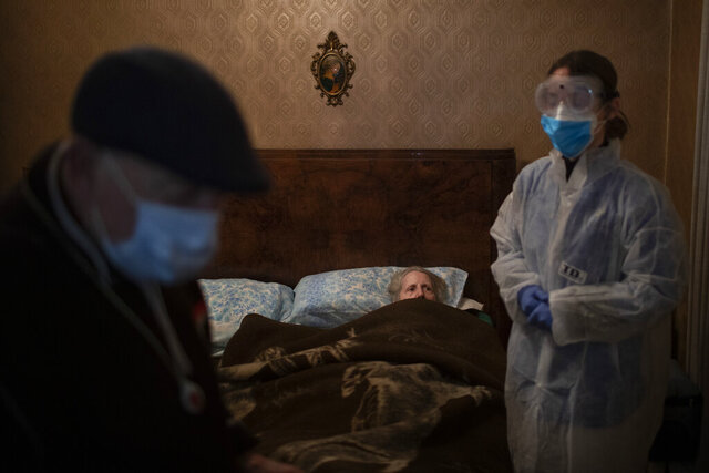 Josefa Ribas, 86, who is bedridden, looks at nurse Alba Rodriguez as Ribas' husband, Jose Marcos, 89, stands by in their home in Barcelona, Spain, March 30, 2020, during the coronavirus outbreak. Ribas suffers from dementia, and Marcos fears for them both if the virus enters their home.