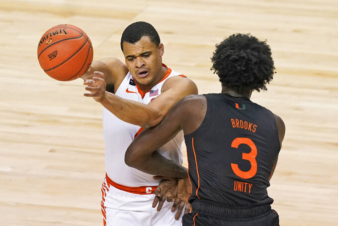 Clemson guard Nick Honor, left, passes the ball as Miami center Nysier Brooks (3) defends during the first half of an NCAA college basketball game in the second round of the Atlantic Coast Conference tournament in Greensboro, N.C., Wednesday, March 10, 2021. (AP Photo/Gerry Broome)