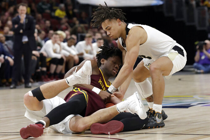 Minnesota's Daniel Oturu and Purdue's Carsen Edwards, right, battle for a loose ball on top of Purdue's Grady Eifert during the first half of an NCAA college basketball game in the quarterfinals of the Big Ten Conference tournament, Friday, March 15, 2019, in Chicago. (AP Photo/Nam Y. Huh)