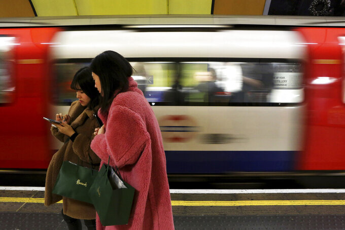 FILE - In this file photo dated Tuesday, Dec. 24, 2019, women use a cell phone on an underground platform in central London.  Facebook's purchase of Giphy will hurt competition for animated images, U.K. regulators said Thursday Aug. 12, 2021, following an investigation, indicating the social network could be forced to sell off the company if the provisional finding's concerns are confirmed.  Giphy's library of short looping videos, or GIFs, are a popular tool for internet users sending messages or posting on social media. (AP Photo/Petros Karadjias, FILE)