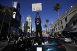 A demonstrator climbs on a car and holds a sign Sunday June, 7, 2020 in the Hollywood area of Los Angeles, during a protest over the death of George Floyd who died May 25 after he was restrained by Minneapolis police. (AP Photo/Marcio Jose Sanchez)