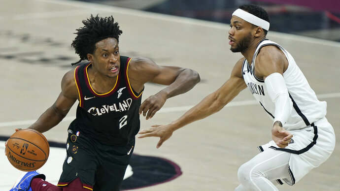 Cleveland Cavaliers' Collin Sexton, left, drives past Brooklyn Nets' Bruce Brown during the first half of an NBA basketball game, Wednesday, Jan. 20, 2021, in Cleveland. (AP Photo/Tony Dejak)