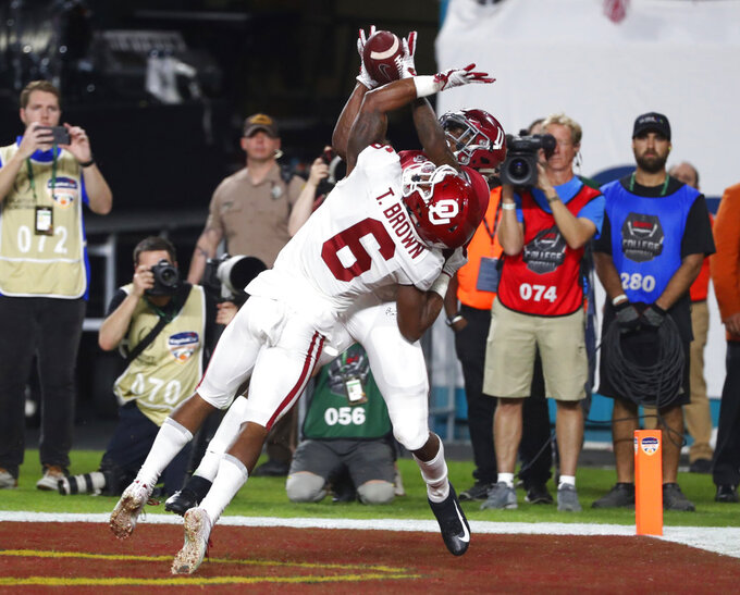 Alabama wide receiver Henry Ruggs III (11) catches a pass in the end zone for touchdown as Oklahoma cornerback Tre Brown (6) defends, during the first half of the Orange Bowl NCAA college football game, Saturday, Dec. 29, 2018, in Miami Gardens, Fla. (AP Photo/Wilfredo Lee)
