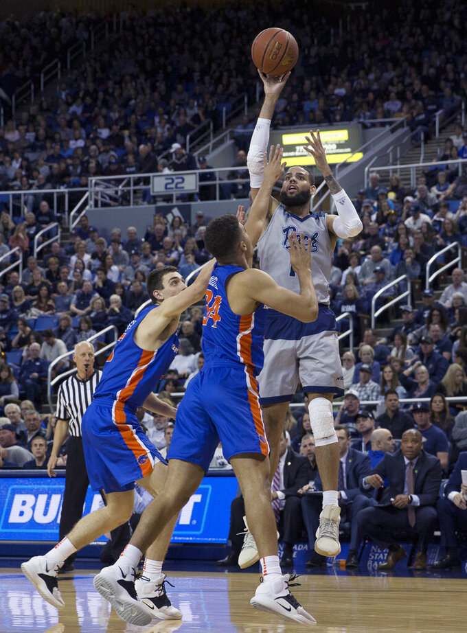 Nevada forward Cody Martin, right, shoots over the Boise State defense in the first half of an NCAA college basketball game in Reno, Nev., Saturday, Feb. 2, 2019. (AP Photo/Tom R. Smedes)
