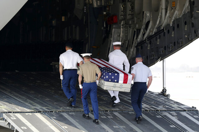 U.S. military guard of honor carry a coffin covered with U.S. national flag during a repatriation ceremony at Mandalay International Airport Thursday, March 12, 2020, in Mandalay, central Myanmar.  The U.S. military has repatriated what may be the remains of service personnel who were lost in action during World War II.  The U.S. Embassy said the remains from Myanmar's central Sagaing region were repatriated at the ceremony at the airport after being recovered in a mission carried out by the Defense POW/MIA Accounting Agency of the U.S. Department of Defense. (AP Photo/Thein Zaw)