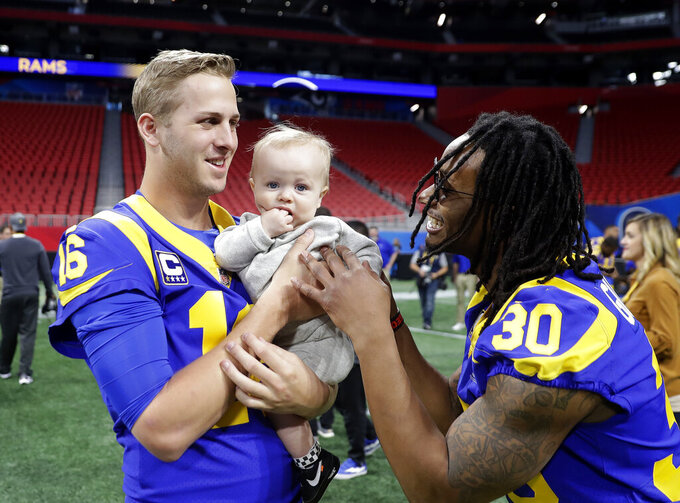 Los Angeles Rams quarterback Jared Goff (16) and running back Todd Gurley (30) play with Cooper Kupp Jr., during walkthrough at the Mercedes Benz Stadium for the NFL Super Bowl 53 football game against the New England Patriots, Saturday, Feb. 2, 2019, in Atlanta. Cooper is the son of Los Angeles Rams wide receiver Cooper Kupp. (AP Photo/John Bazemore)