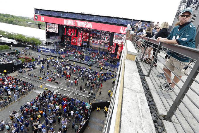 Fans watch the activities on Broadway from a rooftop on the final day of the NFL football draft Saturday, April 27, 2019, in Nashville, Tenn. (AP Photo/Mark Humphrey)