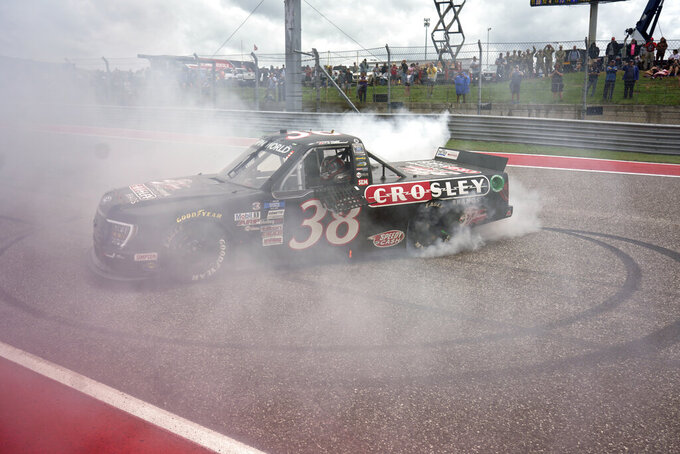 Todd Gilliland performs a burnout after winning the NASCAR Truck Series auto race at the Circuit of the Americas in Austin, Texas, Saturday, May 22, 2021. (AP Photo/Chuck Burton)
