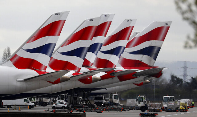 FILE - In this Wednesday, March 18, 2020 file photo, British Airways planes parked at Terminal 5 Heathrow airport in London. British Airways' parent company said Thursday, Sept. 10, 2020 it is to cut flights due to coronavirus travel restrictions and quarantine requirements and confirmed that it is raising 2.7 billion euros ($3.2 billion) through the sale of new shares. (AP Photo/Frank Augstein, File)
